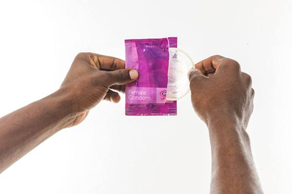 FC2 Female Condom hands opening package, clear