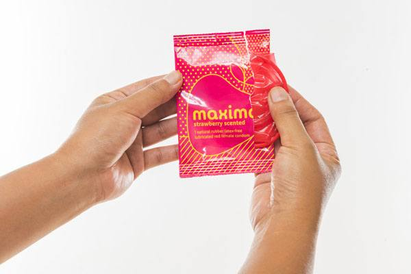 Maxima Female Condom, hands opening package, strawberry