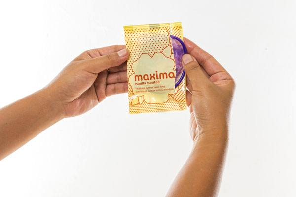 Maxima Female Condom, hands opening package, vanilla