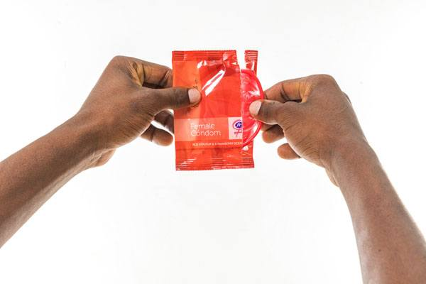 FC2 Female Condom, hands opening package, red