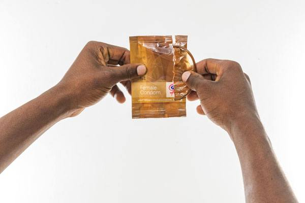 FC2 Female Condom, hands opening package, light brown