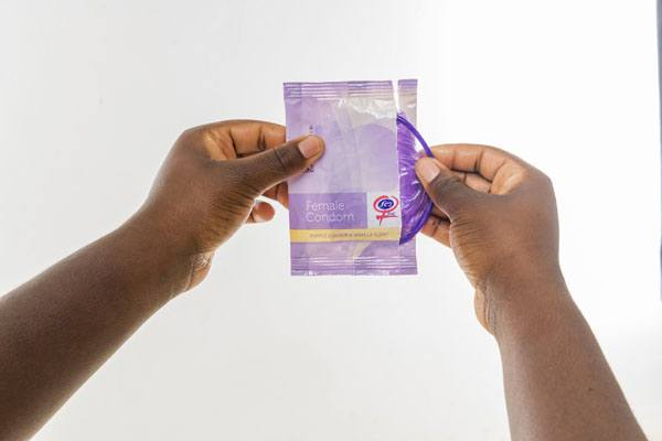 FC2 Female Condom, hands opening package, purple