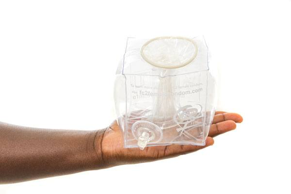 hands holding FC2 Female Condom, in O-Cube, clear