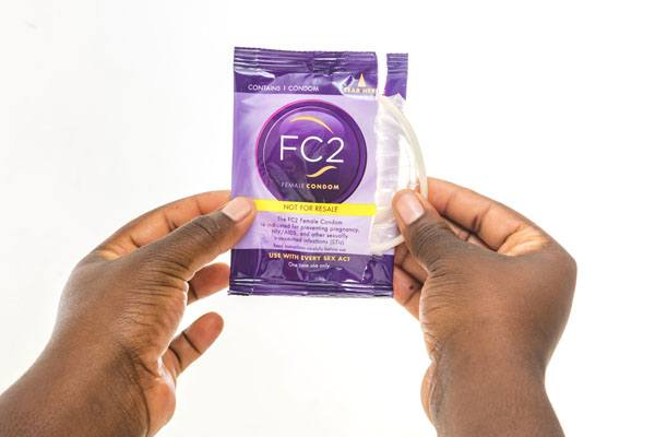 FC2 Female Condom hands opening Not for Resale package, clear